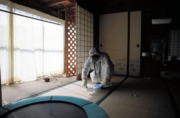 放射線量を測定するため屋内のチリを集める石井さん=2020年10月、福島県浪江町津島地区、三浦英之撮影