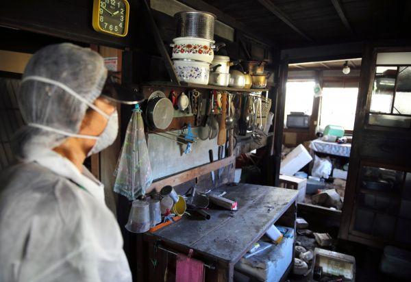 かつて使った料理道具を見つめる石井さん=2020年10月、福島県浪江町津島地区、三浦英之撮影