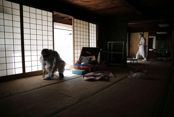 放射線量を測定するため屋内のチリを集める石井ひろみさん=2020年10月、福島県浪江町津島地区、三浦英之撮影