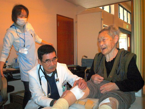 避難先の臨時診療所で避難者の診察をする関根俊二さん(中央)=2011年4月、福島県二本松市、田内康介撮影