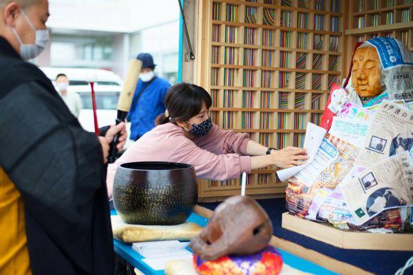 大仏の建設費などをある目ル「勧進キャラバン」の一幕。新型コロナウイルスの影響により中止になったイベントのチラシなどを、等身大の仏像に貼り付ける女性