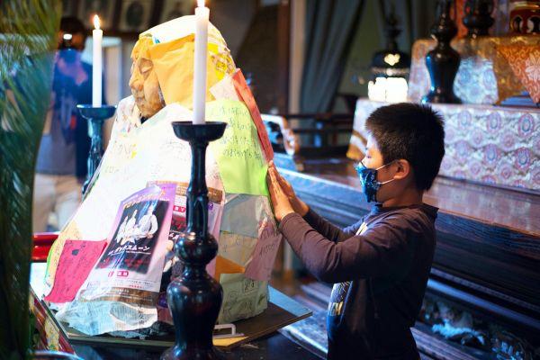 大仏の建設費などをある目ル「勧進キャラバン」の一幕。新型コロナウイルスの影響により中止になったイベントのチラシなどを、等身大の仏像に貼り付ける男の子