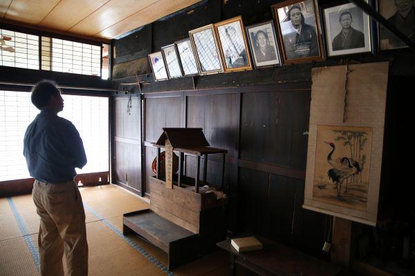 大広間で先祖の写真を見上げる紺野さん=2020年7月、福島県浪江町、三浦英之撮影