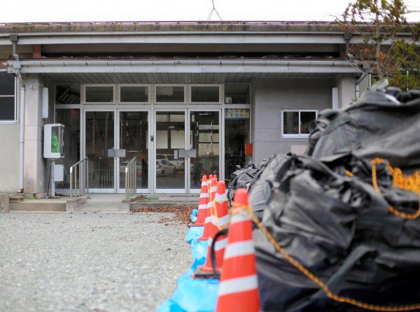 かつて児童クラブが入っていた津島公民館の前には今、黒いフレコンバッグが積み上げられていた=2020年12月、福島県浪江町、三浦英之撮影
