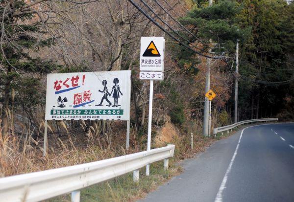 女川原発近くの道路に設置されている「津波浸水区間」の標識と「なくせ! 原発」の看板=2020年11月、宮城県女川町、三浦英之撮影