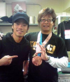 高橋選手(左)が獲得したバンクーバー五輪の銅メダルを手に記念撮影する田山裕士さん