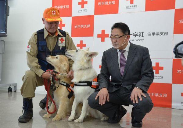 災害救助犬のゆきとさちの飼い主佐々木光義さん(左)と「我々の一員」と話す平野直・日本赤十字社岩手県支部事務局長