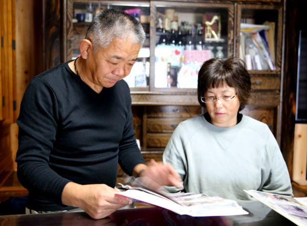 家族のアルバムを見つめながら震災後の10年間を振り返る柴田夫妻=2020年11月、福島県二本松市、三浦英之撮影