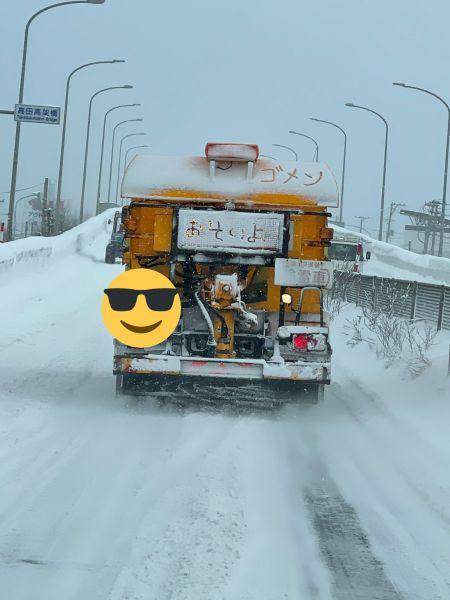 青森県弘前市を走り、車体に降り積もった雪に「おそいよ」「ゴメン」と書かれた除雪車