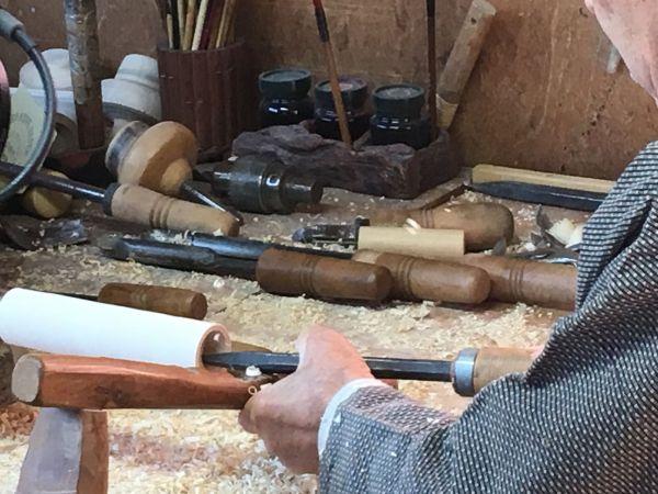 明かりこけしの製作風景。ろくろと呼ばれる道具の上に木材を載せ、刃物で人型に切り出していく