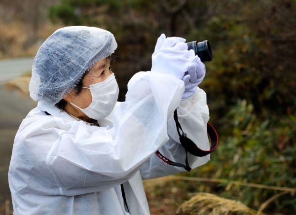 荒れ果てた故郷の姿を写真で記録する馬場靖子さん=2020年12月、福島県浪江町、三浦英之撮影