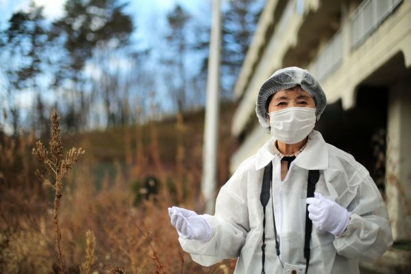 枯れ草に覆われた津島小の校舎の前に立つ馬場靖子さん=2020年12月、福島県浪江町津島地区、三浦英之撮影