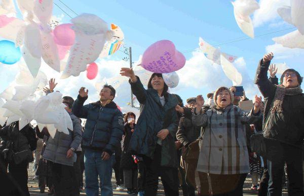 名取市閖上で、メッセージを書いた風船を飛ばす遺族ら=2017年3月11日
