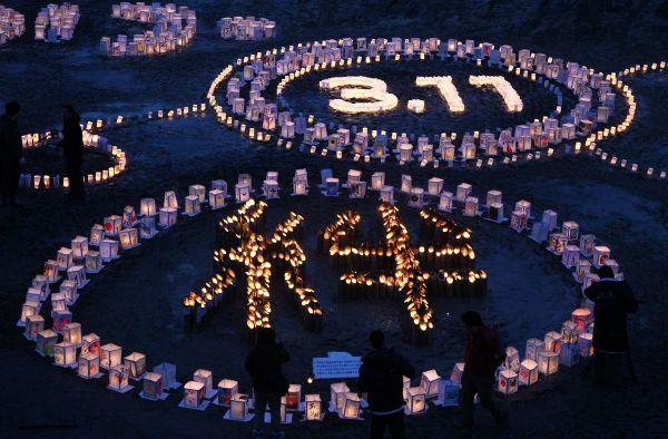 名取市の閖上中学校の校庭に灯籠(とうろう)のあかりで浮かび上がった「絆」と「3・11」の文字=2012年3月11日