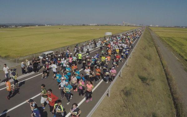 東北・みやぎ復興マラソンで、岩沼市のかさ上げ道路を走るランナーたち。地元の住民が沿道から応援した=2017年10月1日