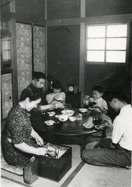 1948年、戦後、一家そろっての食事風景。 畳の上に丸いテーブルがあり、まわりに家族が座っている