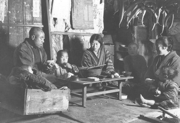 1934年12月、東北地方の農民の食事風景。厳しい冷害に見舞われ、稲は凶作となり、農民は飢饉にひんした。腹を満たすため、屑米に大根葉の食事をする岩手県の家族
