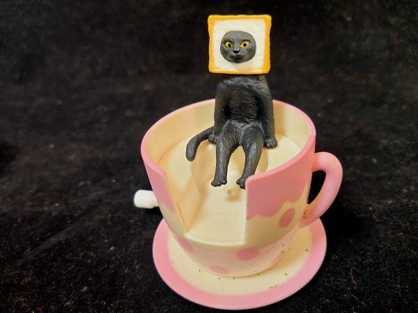 「まわる!コーヒーカップ」に「座る変な猫」