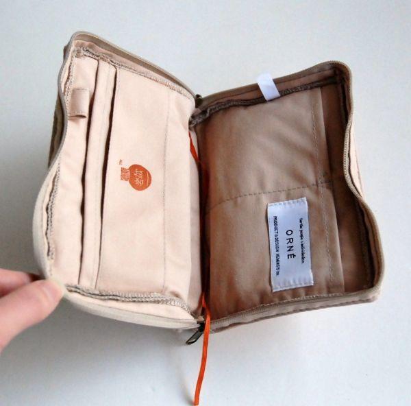 ファスナーを開けると、大きさが異なる四つのポケットが登場。ブックカバーとして使えるよう、表紙を固定するためのベルトや、しおりひもも備えている。