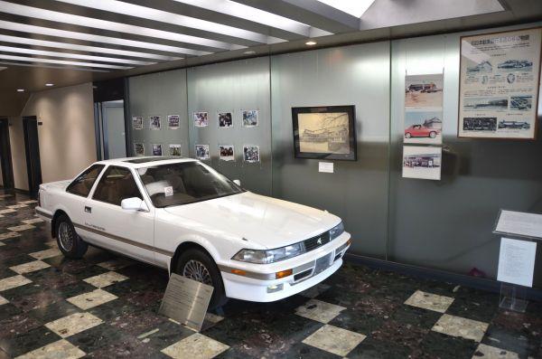 玄関ロビーには建物の歴史を伝える展示パネルがある。コンクールコンディションでディスプレイされる2代目ソアラは、社が所有する貴重な未登録車