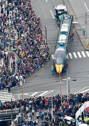 多くの人が見守る中、陸上輸送される英国向け高速鉄道車両=下松市、日吉健吾撮影