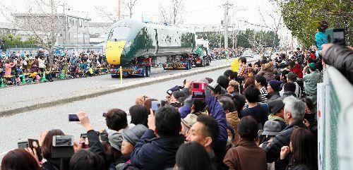 多くの人が見守る中、陸送される高速鉄道車両