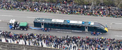 多くの人が見守る中、陸上輸送される英国向け高速鉄道車両=下松市、朝日新聞ヘリから、日吉健吾撮影