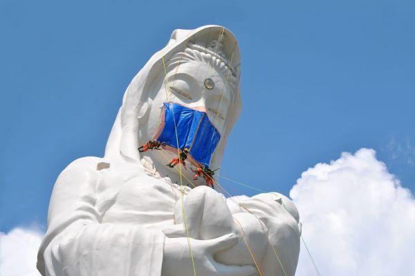 福島県会津若松市にそびえる、高さ57メートルの会津慈母観音。作業員たちが、新型コロナウイルス終息を願う「マスク」を取り付けている。