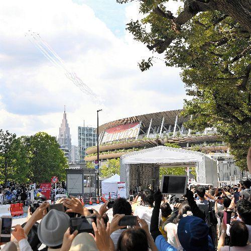 東京五輪の開会式を前に国立競技場上空付近を飛行するブルーインパルス=2021年7月23日午後0時41分、伊藤進之介撮影