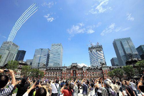 東京駅上空を飛行するブルーインパルス=2021年7月23日、東京都千代田区、長島一浩撮影
