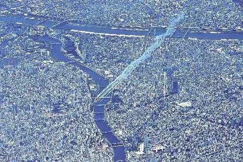 東京上空を編隊飛行する航空自衛隊のアクロバット飛行チーム「ブルーインパルス」=2021年7月23日午後0時53分、朝日新聞社機から、井手さゆり撮影