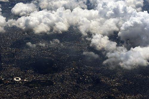 東京上空を編隊飛行する航空自衛隊のアクロバット飛行チーム「ブルーインパルス」=2021年7月23日、朝日新聞社機から、井手さゆり撮影