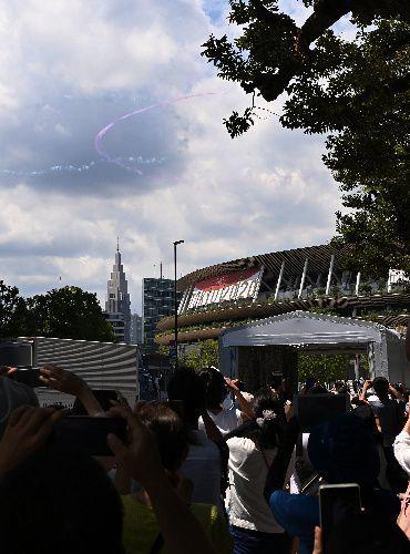 東京五輪の開会式を前に国立競技場上空付近で五輪マークを描くブルーインパルス=2021年7月23日午後0時49分、都心上空、伊藤進之介撮影