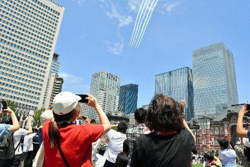 東京駅前でブルーインパルスを見る人たち=2021年7月23日午後0時43分、東京駅前