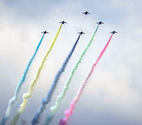 五色のスモークを出して飛行する航空自衛隊のアクロバット飛行チーム「ブルーインパルス」=2021年7月23日午後0時41分、東京都渋谷区の原宿駅前、西畑志朗撮影
