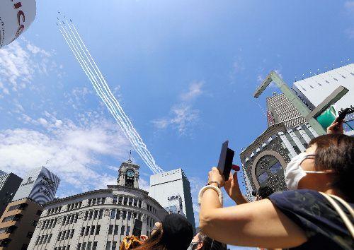 都心上空を飛行するブルーインパルス=2021年7月23日午後0時53分、東京・銀座、川村直子撮影