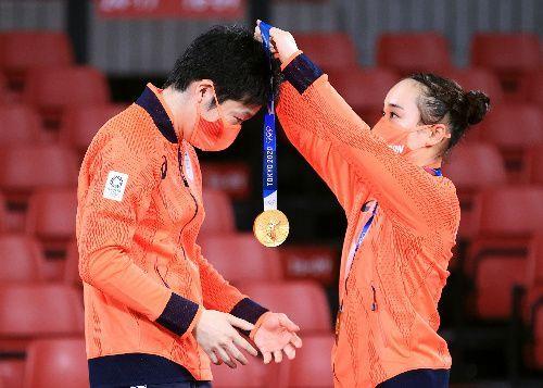 混合ダブルスを制し、表彰式で金メダルを水谷隼(左)にかける伊藤美誠=2021年7月26日、東京体育館、長島一浩撮影