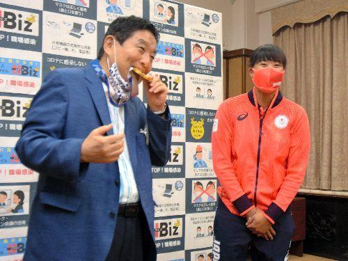 河村たかし・名古屋市長(左)が、東京五輪ソフトボールの金メダルを突然かじった。手渡した後藤希友投手は一瞬驚いた顔をみせた=2021年8月4日午前10時1分、名古屋市役所、関謙次撮影