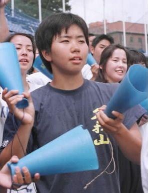 メガホンを持ちスタンドから応援する国学院久我山高校時代の田村知佳さん=1997年7月26日、神宮で