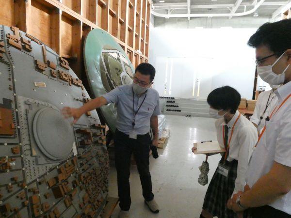 竹中技術研究所の風洞実験室で担当者から説明を聞く浅倉ゆいさん(中)