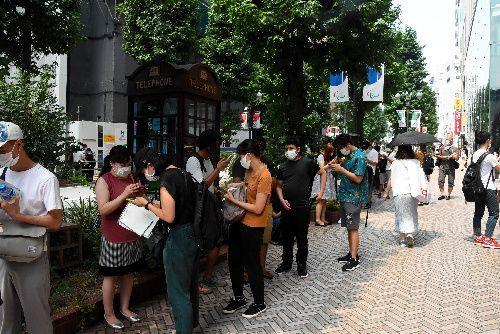 LINEやツイッター上で抽選結果が発表された午前11時50分ごろ、会場前の路上でスマホを片手に自分の抽選券の番号があるか確認する若者たち=2021年8月28日午前11時54分、東京都渋谷区神南1丁目、