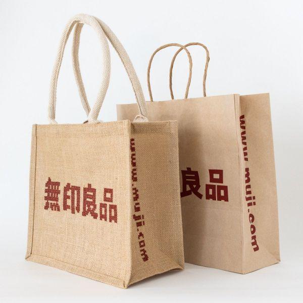 大図まことさんが刺繡を施したジュートバッグ(左)と、無印良品の紙袋