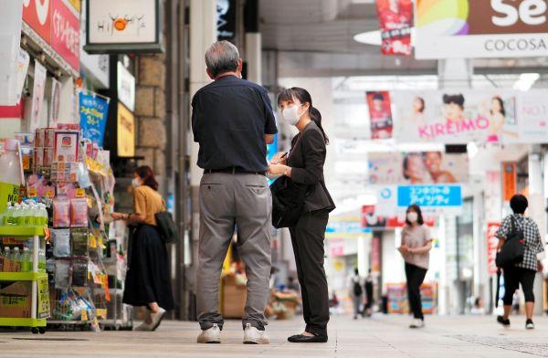 商店街で取材をする堀越理菜記者=2021年9月30日午前10時35分、熊本市、藤脇正真撮影