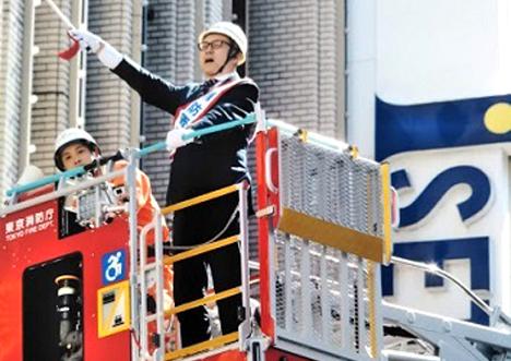 一日消防署長として消火活動の指揮をとる伊勢丹新宿本店長