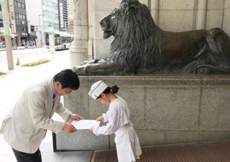 ライオン像の横で修了証授与