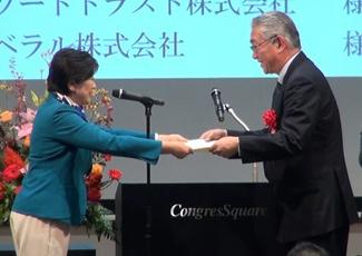 小池 百合子 東京都知事(左)より表彰状を授与された三越伊勢丹ソレイユ 社長(右)