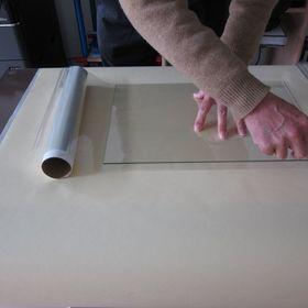 ③広げた新聞紙の上で、フィルムをカット(ガラスサイズより4~5mm小さく)