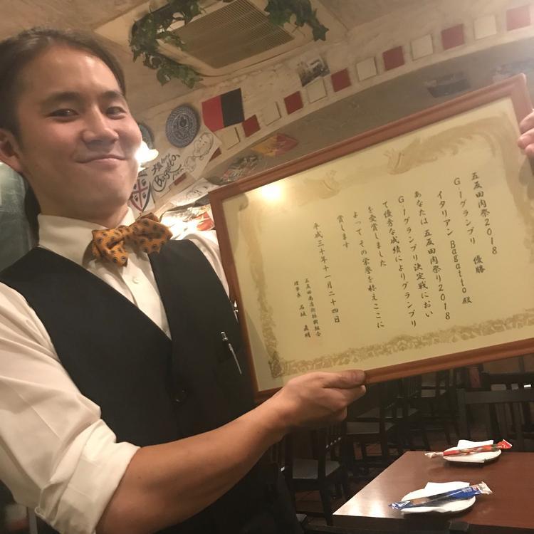 肉フェス優勝時の賞状を掲げるマネージャー