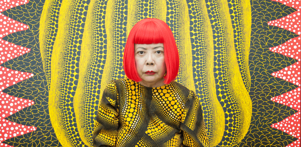 """The artist Yayoi Kusama stands against one of her art pieces. Both her outfit and her art piece are covered in repetitive dot patterns which she has termed """"infinity net""""."""