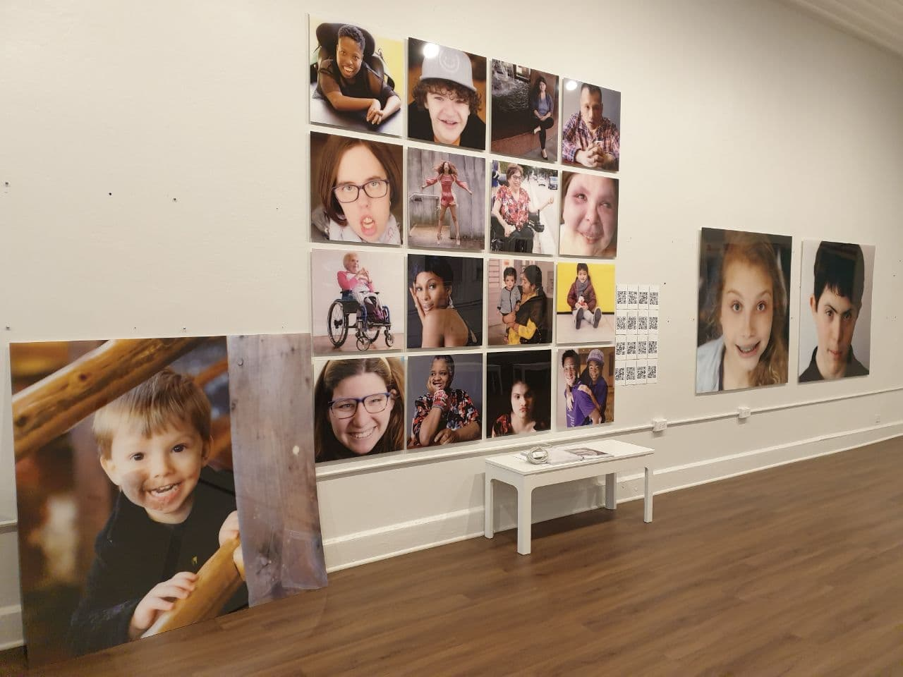 A scene from Positive Exposure exhibition where photographs of individuals with various physical differences are pasted in a grid on a white wall, with a white bench under it. On the wood floor is another large photograph is leaning against the wall.